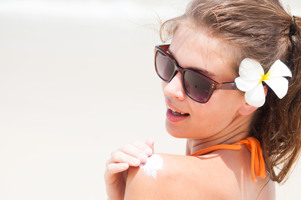Woman applying sunscreen on her shoulder in a beach.