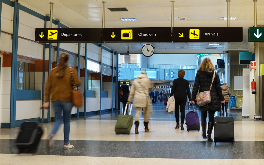 Passengers proceeding towards the security check in an airport.