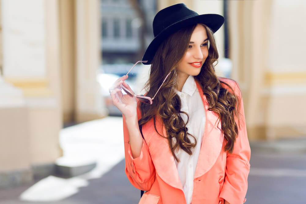 Stylish woman in pink jacket, black hat, and shades