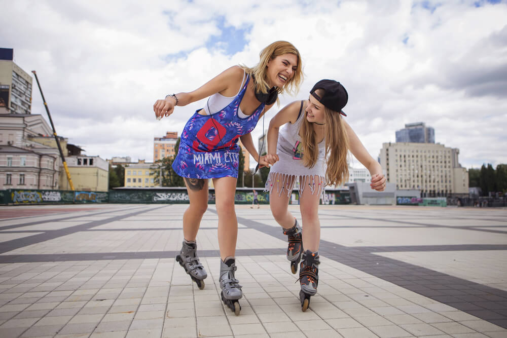 Friends supporting each other while roller skating