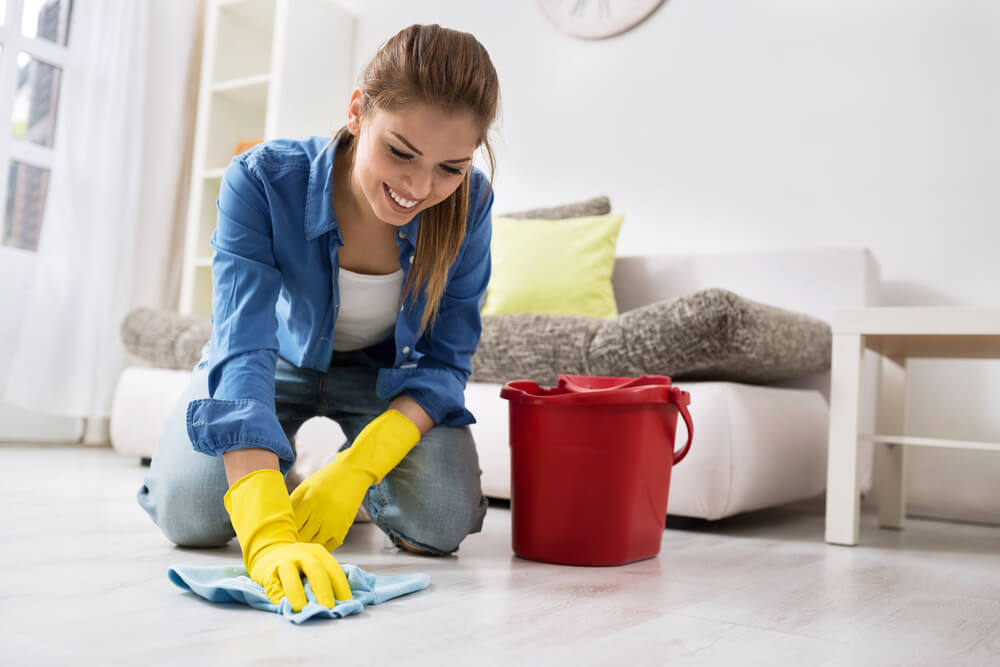 Happy woman cleaning the floor